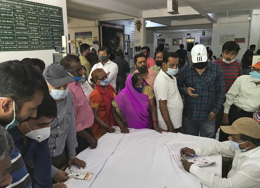 People wait to register themselves to receive the vaccine for COVID-19 at Railway hospital in Prayagraj, India, Saturday, April 10, 2021. India has a seven-day rolling average of more than 100,000 cases per day and has reported 13 million virus cases since the pandemic began, the third-highest total after the United States and Brazil. (AP Photo/Rajesh Kumar Singh)