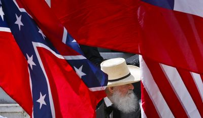 A man sits behind a Confederate flag during a celebration at the Alabama State Capitol to celebrate Confederate Memorial Day in Montgomery, Ala. (AP Photo/Brynn Anderson)
