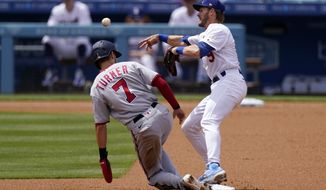 Washington Nationals' Trea Turner, left, is forced out at second as Los Angeles Dodgers second baseman Gavin Lux attempts to throw out Juan Soto at first during the first inning of a baseball game Sunday, April 11, 2021, in Los Angeles. Soto was safe at first on the play. (AP Photo/Mark J. Terrill)