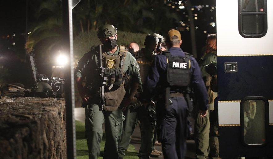 Members of the Honolulu Police Specialized Services Division respond to a barricade situation with an armed man at the Kahala Hotel in Honolulu on Saturday, April 10, 2021. The armed man barricaded himself inside a hotel room at the resort in Honolulu and fired shots through the door, a police official said. (Cindy Ellen Russell/Honolulu Star-Advertiser via AP)