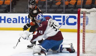 Anaheim Ducks center Adam Henrique, top, tries to deflect the puck in front of Colorado Avalanche goaltender Jonas Johansson in the second period of an NHL hockey game in Anaheim, Calif., Sunday, April 11, 2021. (AP Photo/Kyusung Gong)