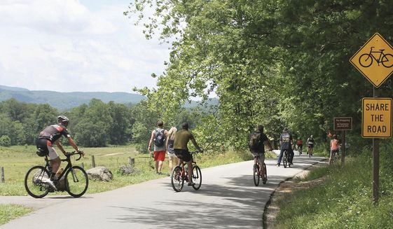 FILE - In this June 24, 2020 file photo, bicyclists start the ride around the Cades Cove Loop Road in The Great Smoky Mountains National Park, in Tenn. The outdoors has offered comfort and escape for many Southerners this year. The sudden isolation of being cut off from family, co-workers, and friends during the pandemic has driven more people to nature as an escape from the confines of the living room. (Tom Sherlin/The Daily Times via AP)