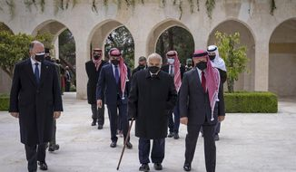 This photo from the Royal Court twitter account, shows Jordan's King Abdullah II, second right, Prince Hamzah bin Al Hussein, fourth right in blue mask, Prince Hassan bin Talal, fifth right, and others arriving to visit the tombs of former kings, in Amman, Jordan, Sunday, April 11, 2021. King Abdullah II and his half brother Prince Hamzah have made their first joint public appearance since a palace feud last week. Members of the Jordanian royal family Sunday marked the centenary of the establishment of the Emirate of Transjordan, a British protectorate that preceded the kingdom. (Royal Court Twitter Account via AP)
