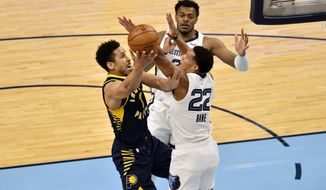 Indiana Pacers guard Malcolm Brogdon (7) shoots against Memphis Grizzlies guard Desmond Bane (22) and center Xavier Tillman (2)in the second half of an NBA basketball game Sunday, April 11, 2021, in Memphis, Tenn. (AP Photo/Brandon Dill)