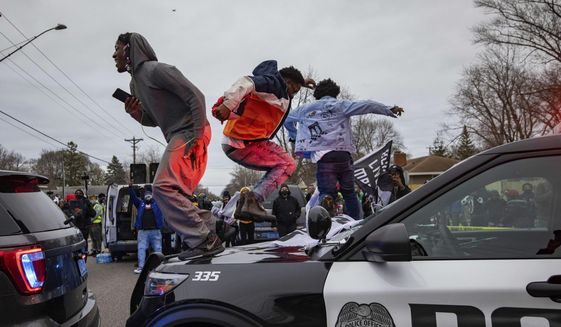 Men jump on the hood of a police car after a family said a man was shot and killed by law enforcement on Sunday, April 11, 2021, in Brooklyn Center, Minn. (AP Photo/Christian Monterrosa)
