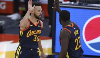 Golden State Warriors guard Stephen Curry is congratulated by Draymond Green after making a basket against the Houston Rockets during the second half of an NBA basketball game in San Francisco, Saturday, April 10, 2021. (AP Photo/Jed Jacobsohn)