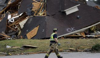 A firefighter surveys damage to a house after a tornado touches down south of Birmingham, Ala., in the Eagle Point community damaging multiple homes Thursday, March 25, 2021. The National Weather Service issued multiple tornado warnings for Alabama and surrounding states. (AP Photo/Butch Dill)
