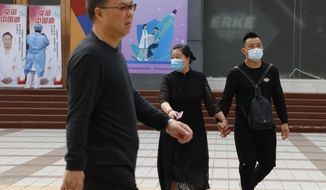 Chinese residents, some wearing masks, pass by a coronavirus vaccination center in Beijing  Friday, April 9, 2021. In a rare admission of the weakness of Chinese coronavirus vaccines, the country's top disease control official says their effectiveness is low and the government is considering mixing them to give them a boost. (AP Photo/Ng Han Guan)