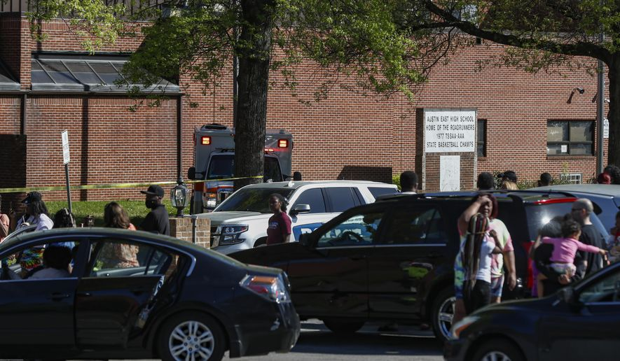People gather outside Austin East High School in Knoxville, Tenn., as Knoxville police work the scene following a shooting at the school Monday, April 12, 2021. (AP Photo/Wade Payne)
