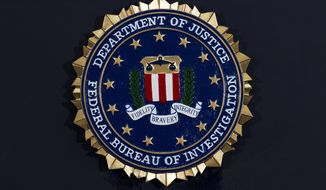 This Thursday, June 14, 2018, file photo, shows the FBI seal at a news conference at FBI headquarters in Washington. (AP Photo/Jose Luis Magana, File)