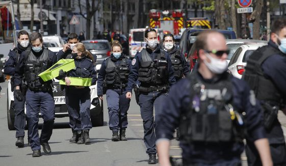 Police officers leave the scene after a shooting Monday, April 12, 2021 in Paris. A gunman has shot two people in front of a hospital in Paris and the attacker fled on a motorcycle. (AP Photo/Christophe Ena)