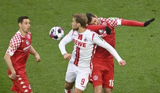 Cologne's Sebastian Andersson, centre, and Mainz's Stefan Bell fight for the ball, during the German Bundesliga soccer match between Cologne and Mainz, at Rhein-Energie-Stadion, in Cologne, Germany, Sunday, April 11, 2021. (Federico Gambarini/dpa via AP)