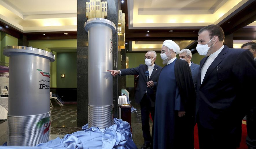 In this April 10, 2021, file photo released by the official website of the office of the Iranian presidency, Iranian President Hassan Rouhani, second from right, listens to the head of the Atomic Energy Organization of Iran Ali Akbar Salehi while visiting an exhibition of Iran's new nuclear achievements in Tehran, Iran. Iran's nuclear program has been targeted by diplomatic efforts and sabotage attacks over the last decade, with the latest incident striking its underground Natanz facility. The attack Sunday, April 11, 2021 at Natanz comes as world powers try to negotiate a return by Iran and the U.S. to Tehran's atomic accord. (Iranian Presidency Office via AP) **FILE**