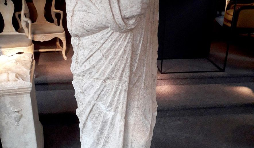 This image released on Monday, April 12, 2021 by the Carabinieri (Italian paramilitary police) art squad's archaeological unit, shows a headless Roman statue wearing a draped toga recovered in Brussels on Wednesday, Feb. 3, 2021. Italian police say they have recovered a 1st century Roman statue that was stolen from an archaeological site in 2011 and found in a Belgian antiques shop by two off-duty Italian art squad police officers. The Carabinieri art squad said Monday that an Italian businessman who used a Spanish pseudonym has been referred to prosecutors for further investigation into allegations he received and then exported the statue abroad. The statue has been valued at 100,000 euro. (Carabinieri via AP)