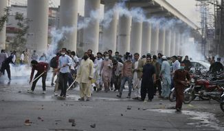 Angry supporters of Tehreek-e-Labiak Pakistan, a radical Islamist political party, throw stones towards police firing tear gas to disperse them, at a protest against the arrest of their leader Saad Rizvi, in Lahore, Pakistan, Monday, April 12, 2021. Pakistan police arrested Rizvi a day after he threatened the government with protests if it did not expel France's ambassador over depictions of Islam's Prophet Muhammad. (AP Photo/K.M. Chaudary)