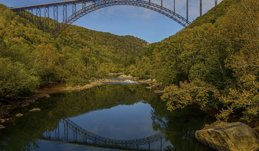 FILE - In this Oct. 9, 2019 file photo, the New River Gorge Bridge is seen from Fayette Station in Fayetteville, W.Va. A program launched Monday, April 12, 2021, will try to lure outdoor enthusiasts to live and work in West Virginia with enticements of $12,000 cash and free passes for a year for recreation destinations such as whitewater rafting and golf.. (F. Brian Ferguson/Charleston Gazette-Mail via AP, File)