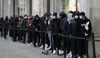 A queue grows big as people wait to enter a Nike Town shop on Oxford Street in London, early Monday morning, April 12, 2021. Millions of people in England will get their first chance in months for haircuts, casual shopping and restaurant meals on Monday, as the government takes the next step on its lockdown-lifting road map. (AP Photo/Kirsty Wigglesworth)