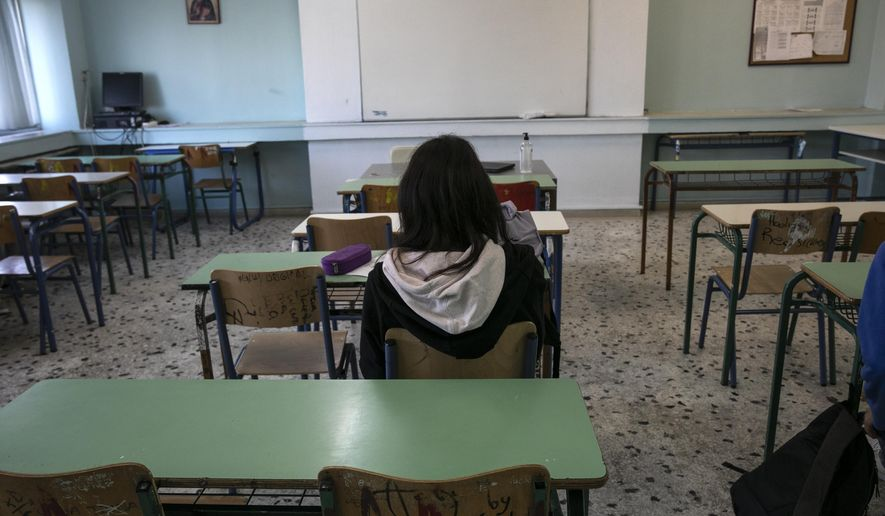 A high school student sits inside a classroom at Glyfada, suburb west of Athens, Monday, April 12, 2021. Home tests have been distributed to teachers and students aged 16-18, as authorities reopened high schools for students in the final three grades on Monday. (AP Photo/Yorgos Karahalis)