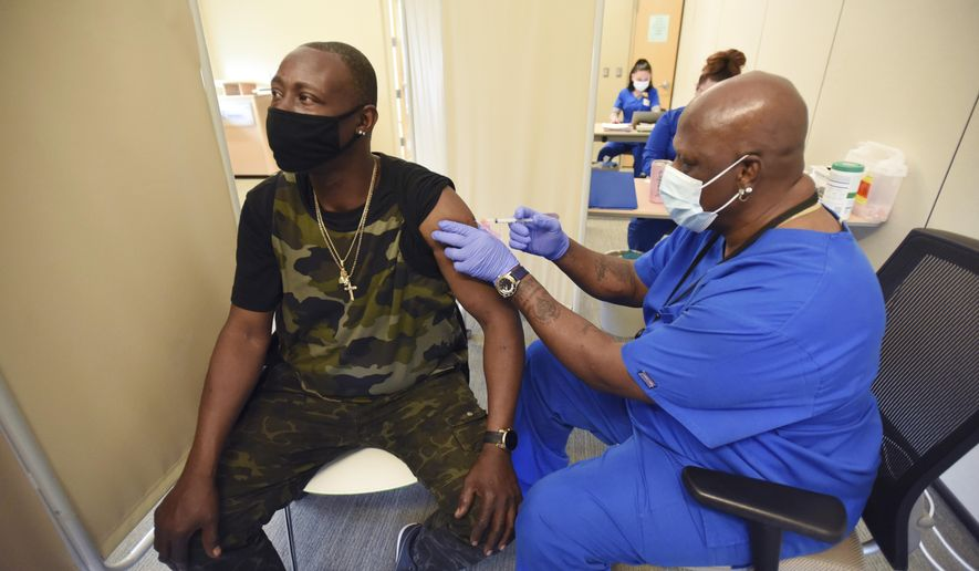 Certified medical assistant Vernest Lacy administers a second dose of the Moderna COVID-19 vaccine to Theodore Heggler, of Benton Harbor, Mich., at InterCare Community Health Network, Friday, April 9, 2021, in Benton Harbor, Mich. (Don Campbell/The Herald-Palladium via AP)