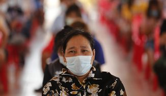 People wait for the the Sinovac COVID-19 vaccination in Bangkok, Thailand, Monday, April 12, 2021. Thailand's Health Ministry warned Sunday that restrictions may need to be tightened to slow the spread of a fresh coronavirus wave, as the country hit a daily record for new cases. (AP Photo/Sakchai Lalit)