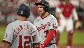 Washington Nationals' Trea Turner (7) is congratulated by teammate Kyle Schwarber (12) after scoring during the third inning of a baseball game against the St. Louis Cardinals Tuesday, April 13, 2021, in St. Louis. (AP Photo/Jeff Roberson)