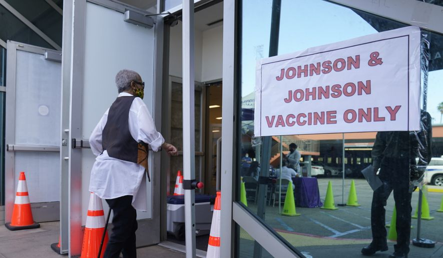 "In this April 1, 2021, photo, people walk in to get their COVID-19 vaccine at the Baldwin Hills Crenshaw Plaza past a sign that says ""Johnson & Johnson vaccine only"" in Los Angeles. U.S. health regulators on Tuesday, April 13, is recommending a pause in using the vaccine to investigate reports of potentially dangerous blood clots. (AP Photo/Damian Dovarganes) **FILE**"