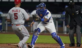 Kansas City Royals catcher Salvador Perez, right, forces out Los Angeles Angels Albert Pujols (5) during the sixth inning of a baseball game at Kauffman Stadium in Kansas City, Mo., Tuesday, April 13, 2021. (AP Photo/Orlin Wagner)