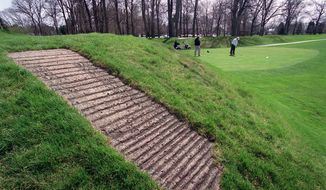 FILE - This April 6, 2000 file photo shows a concrete walkway, foreground, that allows golfers access to the top of an ancient American Indian mound at Moundbuilders Country Club in Newark, Ohio. The Ohio Supreme Court is scheduled to hear oral arguments Tuesday, April 13, 2021 in the debate over public access to the set of ancient ceremonial and burial earthworks. The case pits the state historical society against the country club where the earthworks are located. (Jeff Adkins/The Columbus Dispatch via AP, File)