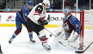 Arizona Coyotes left wing Lawson Crouse, center, drives past Colorado Avalanche defenseman Cale Makar, left, to shoot against Avalanche goaltender Philipp Grubauer in the third period of an NHL hockey game Monday, April 12, 2021, in Denver. (AP Photo/David Zalubowski)