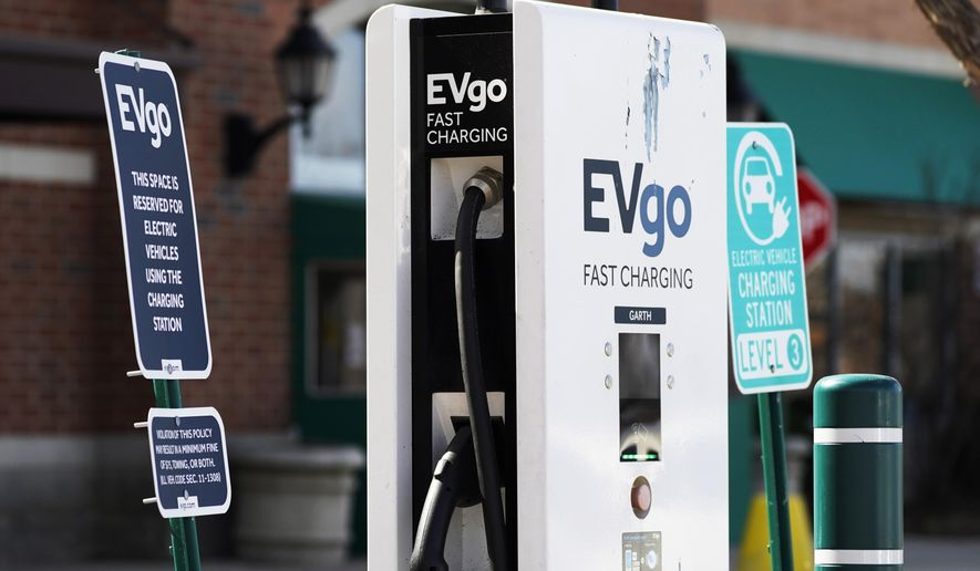 """FILE - This March 31, 2021 file photo shows a EVgo electric vehicle charging station  at Willow Festival shopping plaza parking lot in Northbrook, Ill.    The European Union is lacking sufficient charging infrastructure for electric vehicles, according to the bloc's external auditor. In a report published Tuesday, April 13, 2021, the European Court of Auditors said users are gaining more harmonized access to charging networks but the EU is still """"a long way from reaching its Green Deal target of 1 million charging points by 2025.""""  (AP Photo/Nam Y. Huh, File)"""