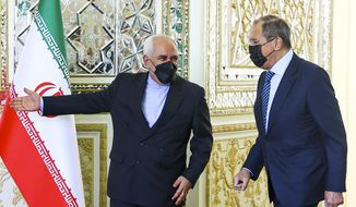 In this photo released by Russian Foreign Ministry Press Service, Iranian Foreign Minister Mohammad Javad Zarif, left, welcomes Russian Foreign Minister Sergey Lavrov for the talks in Tehran, Iran, Tuesday, April 13, 2021. Iran's foreign minister warned Tuesday that an attack on its main nuclear enrichment site at Natanz affects ongoing negotiations in Vienna over its tattered atomic deal with world powers.  (Russian Foreign Ministry Press Service via AP)