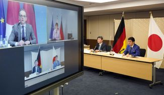 "Japanese Foreign Minister Toshimitsu Motegi, second from right, and Defense Minister Nobuo Kishi, right, attend a video conference with German Foreign Minister Heiko Maas, top left on screen, and German Defense Minister Annegret Kramp-Karrenbauer, top right on screen, at Foreign Ministry in Tokyo during their ""2 plus 2"" ministerial meeting Tuesday, April 13, 2021. (Frank Robichon/Pool Photo via AP)"