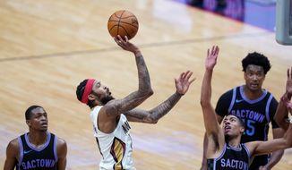 New Orleans Pelicans forward Brandon Ingram (14) shoots over Sacramento Kings guard Tyrese Haliburton, right, in the second half of an NBA basketball game in New Orleans, Monday, April 12, 2021. The Pelicans won 117-110. (AP Photo/Gerald Herbert)