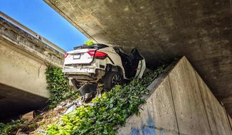 This photo provided by the California Highway Patrol shows the scene where a man fleeing from the CHP totaled his girlfriend's Maserati SUV after he careened up an embankment and slammed into the underside of an overpass, wedging the car under a freeway in Oakland, Calif., on Monday, April 12, 2021. (California Highway Patrol via AP)