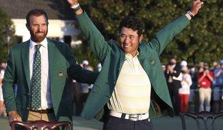 Hideki Matsuyama, of Japan, celebrates while wearing the champion's green jacket as Dustin Johnson looks on after winning the Masters golf tournament on Sunday, April 11, 2021, in Augusta, Ga. (Curtis Compton/Atlanta Journal-Constitution via AP)