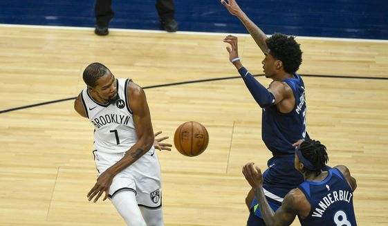 Brooklyn Nets forward Kevin Durant (7)passes the ball behind his back and around Minnesota Timberwolves forward Jaden McDaniels (3) and Timberwolves forward Jarred Vanderbilt (8) during the first half of an NBA basketball game Tuesday, April 13, 2021, in Minneapolis. (AP Photo/Craig Lassig)