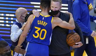 Golden State Warriors guard Stephen Curry (30) hugs head coach Steve Kerr after the Warriors defeated the Denver Nuggets in an NBA basketball game in San Francisco, Monday, April 12, 2021. (AP Photo/Jeff Chiu)