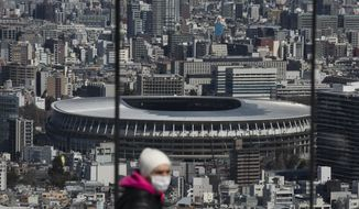 FILE - In this March 3, 2020, file photo, the New National Stadium, a venue for the opening and closing ceremonies at the Tokyo 2020 Olympics, is seen from Shibuya Sky observation deck in Tokyo. Organizers and the International Olympic Committee are pushing on despite COVID-19 risks, myriad scandals, and overwhelming public opposition in Japan to holding the games. (AP Photo/Jae C. Hong, File)