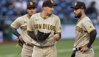 San Diego Padres starting pitcher Blake Snell, center, talks with Eric Hosmer, right, as he waits for manager Jayce Tingler to pull him from the baseball game against the Pittsburgh Pirates during the first inning in Pittsburgh, Tuesday, April 13, 2021. (AP Photo/Gene J. Puskar)