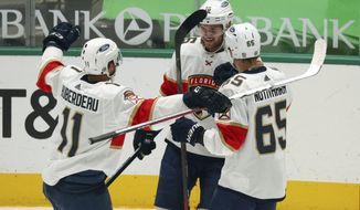 Florida Panthers left wing Jonathan Huberdeau (11) and defenseman Markus Nutivaara (65) celebrate the first-period goal by Aleksander Barkov (16) against the Dallas Stars during an NHL hockey game Tuesday, April 13, 2021, in Dallas. (AP Photo/Richard W. Rodriguez)