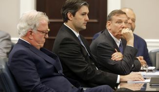 FILE - In this Dec. 5, 2016 file photo, defense attorneys Andy Savage, left, Don McCune, and Miller Shealy, right, sit around former North Charleston police officer Michael Slager at theCharleston County court in Charleston, S.C. Slager, who is serving 20 years in prison for killing an unarmed Black man who was running away from a traffic stop, said his lawyer never told him about a plea offer from prosecutors that could have cut years off his sentence and is asking for a new sentence in federal court this week.  (Grace Beahm/Post and Courier via AP, Pool)