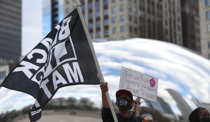 A demonstrator waves a Black Lives Matter flag in front of Chicago's Cloud Gate in Millennium Park during a peaceful protest on Tuesday, April 13, 2021, demanding justice for Daunte Wright, a 20-year-old Black man who was shot dead by police Sunday after a traffic stop in Brooklyn Center, Minn. (AP Photo/Shafkat Anowar) ** FILE **