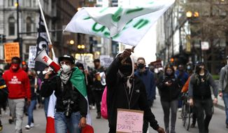 Protestors proceed along Chicago downtown during a peaceful protest on Tuesday, April 13, 2021, demanding justice for Daunte Wright, a 20-year-old Black man who was shot dead by police Sunday after a traffic stop in Brooklyn Center, Minn. (AP Photo/Shafkat Anowar)