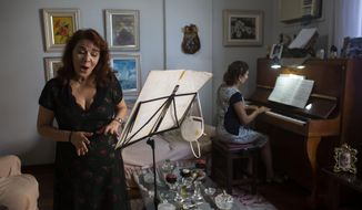 Municipal Theatre soprano opera singer Georgia Szpilman practices at her coach's home during the COVID-19 pandemic in Rio de Janeiro, Brazil, Thursday, March 25, 2021. Szpilman used to perform in the city's majestic municipal theater that has been closed for over a year, but because she is technically a public servant, she was able to keep her salary from Rio's state government while performing online. (AP Photo/Bruna Prado)
