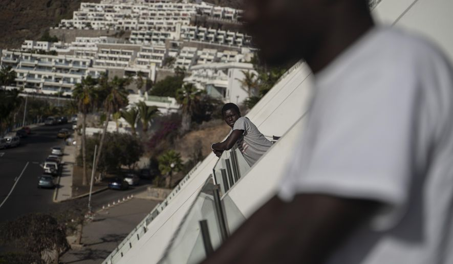 A migrant leans on the balcony of the Holiday Club Puerto Calma hotel in Puerto Rico de Gran Canaria, Spain, April 2, 2021. With hundreds of empty rooms, British hotel director Calvin Lucock and his Norwegian wife Unn Tove Saetran decided to reopen their doors at their own expense to provide food, shelter and care to young migrant men who fell out of the official reception and integration system. (AP Photo/Renata Brito)