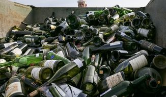 FILE - In this Dec. 10, 2015 file photo more than 500 bottles of counterfeit and unsellable wine are destroyed at the Texas Disposal Systems recycling and compost facility in Austin, Texas. The wine is from the Rudy Kurniawan case, the man convicted of fraud in federal court in 2013 for producing and selling millions of dollars of counterfeit wine. Kurniawan, who bilked wine collectors out of millions by selling cheaper hooch he relabeled in his kitchen has been deported to his native Indonesia. U.S. immigration officials say Kurniawan was deported last week from Dallas/Fort Worth International Airport to Tangerang City. (Rodolfo Gonzalez/Austin American-Statesman via AP,File)