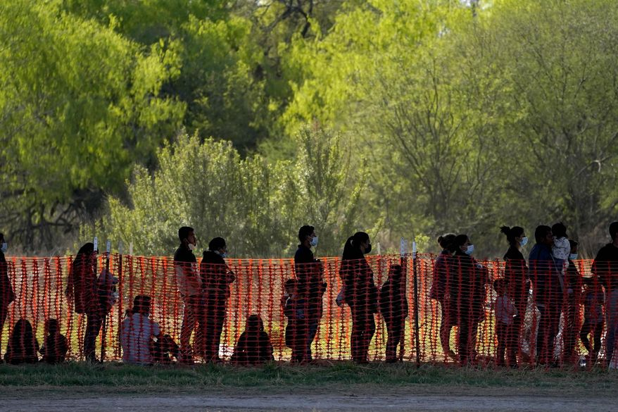 Migrants with children are seen in custody at a U.S. Customs and Border Protection processing area in Mission, Texas, in mid-March. (Associated Press)