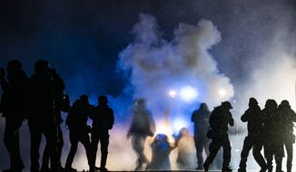 Authorities fire gas munitions at demonstrators gathered outside the Brooklyn Center Police Department to protest the shooting death of Daunte Wright, late Tuesday, April 13, 2021, in Brooklyn Center, Minn. (AP Photo/John Minchillo)