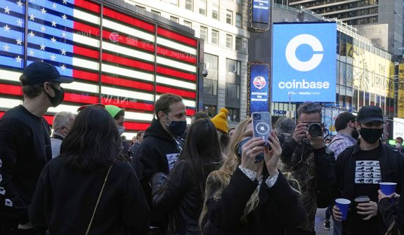 Coinbase employees gather outside the Nasdaq MarketSite during the company's IPO, in New York's Times Square, Wednesday, April 14, 2021. Wall Street will be focused on Coinbase Wednesday with the digital currency exchange becoming a publicly traded company. (AP Photo/Richard Drew)
