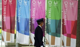 A security guard wearing a protective mask to help curb the spread of the coronavirus walks past banners for the Tokyo 2020 Olympic and Paralympic Games in Tokyo, Wednesday, April 14, 2021, to mark 100 days before the start of the Summer Games. (AP Photo/Eugene Hoshiko)
